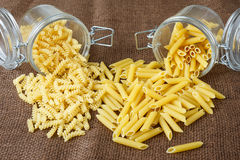 Italian pasta - penne and fusilli in glass jar Stock Images