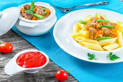 Italian pasta penne and stewed meat royalty free stock images