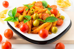 Italian pasta penne in tomato sauce with olives and cherry tomat Stock Images