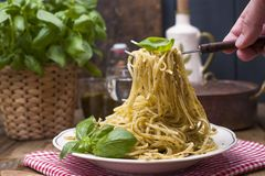 Italian pasta with pesto sauce and fresh basil. A delicious homemade dinner and a man`s hand with a fork in the frame. Photo in a stock images