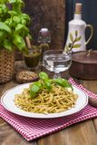 Italian pasta with pesto sauce and fresh basil. A delicious homemade dinner. Photo in a rustic style. Copy space royalty free stock photo