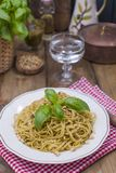 Italian pasta with pesto sauce and fresh basil. A delicious homemade dinner. Photo in a rustic style. Copy space stock photos