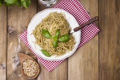 Italian pasta with pesto sauce and fresh basil. A delicious homemade dinner. Photo in a rustic style. Top view. copy space stock photos
