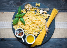 Italian pasta with pesto sauce made with basil leaf. S, pine nuts, fresh garlic and olive oil over an old wood background, top view Stock Image