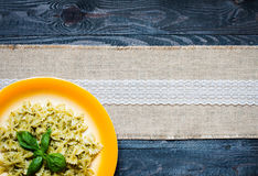Italian pasta with pesto sauce made with basil leaf. S, pine nuts, fresh garlic and olive oil over an old wood background, top view Stock Images