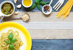 Italian pasta with pesto sauce made with basil leaf. S, pine nuts, fresh garlic and olive oil over an old wood background, top view Royalty Free Stock Photography