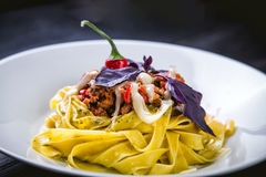 Italian pasta in a plate in a restaurant with chilli Stock Image