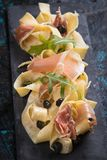 Italian pasta with prosciutto. Italian pasta with cheese sauce and slices of prosciutto smoked ham Royalty Free Stock Images