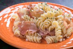 Italian pasta with prosciutto. Italian pasta with cheese sauce and slices of prosciutto smoked ham Stock Image