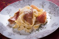Italian pasta with prosciutto. Italian pasta with cheese sauce and slices of prosciutto smoked ham Stock Photography