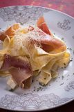 Italian pasta with prosciutto. Italian pasta with cheese sauce and slices of prosciutto smoked ham Royalty Free Stock Photo