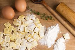 Italian pasta, ravioli with flour eggs and greens. Italian pasta, ravioli with flour eggs, herbs and kitchen utensils Stock Images