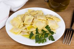 Italian pasta, ravioli with parsley and olive oil. Italian pasta, ravioli with parsley, olive oil and flatware Royalty Free Stock Photography