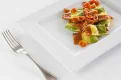Italian pasta, ravioli tricolor with tomato. Homemade tricolor ravioli in white dish in a refined and elegant restaurant. Ravioli have the characteristic colors stock photos
