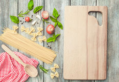 Italian pasta. Raw Italian pasta with tomato sauce ingredients and cutting board Royalty Free Stock Image