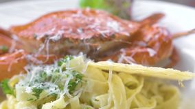 Italian pasta with red crab, fresh herb and cheese on white plate close up. Traditional pasta with seafood in italian stock footage