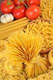 Italian pasta, ripe tomatoes branch and garlic Royalty Free Stock Photo