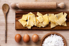 Italian pasta. Rolling pin, flour, eggs, ladle. Wooden surface. Some ingredients to make Italian pasta. Eggs, flour and pasta. All on a wooden surface. Flour in Stock Photo