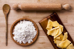 Italian pasta. Rolling pin, flour, ladle. Wooden surface. Royalty Free Stock Photo