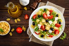 Italian pasta salad with fresh tomato, cheese, lettuce and olives on wooden background. Mediterranean cuisine. Cooking lunch. Hea. Lthy diet food. Top view royalty free stock photos