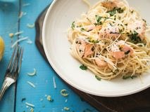 Italian pasta with salmon, parsley, lemon rind and cheese. Fresh pasta with salmon in a creamy sauce in a saucer on a blue wooden royalty free stock photo
