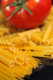 Italian pasta selection and tomato over black Royalty Free Stock Photos