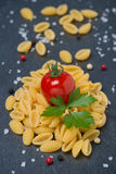Italian pasta shells, cherry tomatoes, salt and pepper Stock Photos