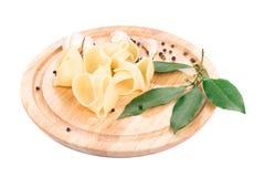 Italian pasta shells on a wood plate. Royalty Free Stock Photo
