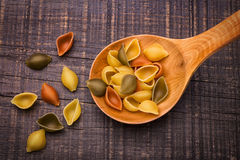 Italian Pasta shells in a wooden spoon. Royalty Free Stock Photography