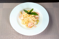 Italian pasta with shrimps. And basil on a plate Stock Images