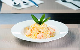 Italian pasta with shrimps. And basil on a plate Royalty Free Stock Photography