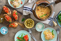 Italian pasta, snacks and salad on a light wooden table. Top view. Italian Dining Table Concept Stock Photos