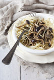Italian pasta spaghetti with fresh pioppini mushrooms on plate on white table with fork Stock Images