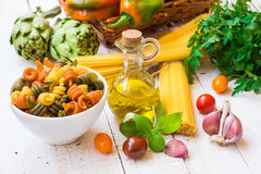 Italian pasta spaghetti fusilli, bottle of olive oil, basil, cherry tomatoes, garlic, herbs and vegetables, dinner ingredients Stock Photography