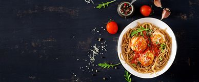 Italian pasta. Spaghetti with meatballs and parmesan cheese. In bowl on dark rustic wood background. Dinner. Banner. Top view. Slow food concept stock photography