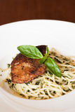 Italian pasta spaghetti with pesto sauce and striped bass Stock Images