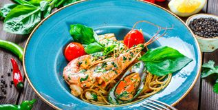 Italian pasta spaghetti with seafood, langoustine, mussels, squid, scallops, shrimp, Parmesan cheese royalty free stock photography