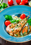 Italian pasta spaghetti with seafood, langoustine, mussels, squid, scallops, shrimp, Parmesan cheese, Stock Image