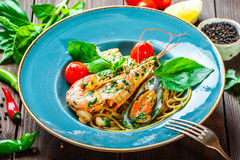Italian pasta spaghetti with seafood, langoustine, mussels, squid, scallops, shrimp, Parmesan cheese, Royalty Free Stock Images
