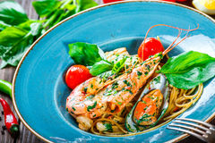 Italian pasta spaghetti with seafood, langoustine, mussels, squid, scallops, shrimp, Parmesan cheese, Royalty Free Stock Image
