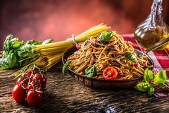 Italian pasta spaghetti with tomato sauce olive oil basil and parmesan cheese in old pan stock photo