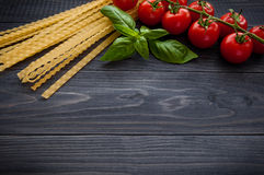 Italian pasta spaghetti and tomatoes with herbs on a wooden table. Spaghetti and tomatoes with herbs on an old and vintage wooden background Royalty Free Stock Image