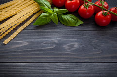 Italian pasta spaghetti and tomatoes with herbs on a wooden table. Spaghetti and tomatoes with herbs on an old and vintage wooden background Stock Photography