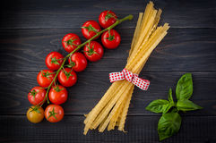 Italian pasta spaghetti and tomatoes with herbs on a wooden table. Spaghetti and tomatoes with herbs on an old and vintage wooden background Stock Image