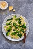Italian pasta with spinach, broccoli and green peas on a concrete background. Dinner time. Top view stock image