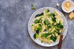 Italian pasta with spinach, broccoli and green peas on a concrete background. Dinner time. Top view stock photography