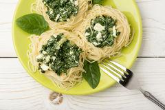 Italian pasta with spinach and feta on green plate on the wooden background. Royalty Free Stock Image