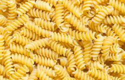 Italian pasta spirals. Close up of Italian pasta spirals forming background stock images