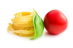 Italian pasta tagliatelle, tomato and basil leaf Stock Photography