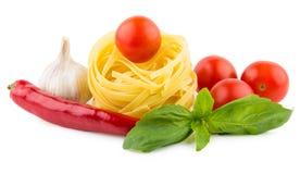 Italian pasta tagliatelle, tomatoes, garlic, chili pepper and ba Stock Image